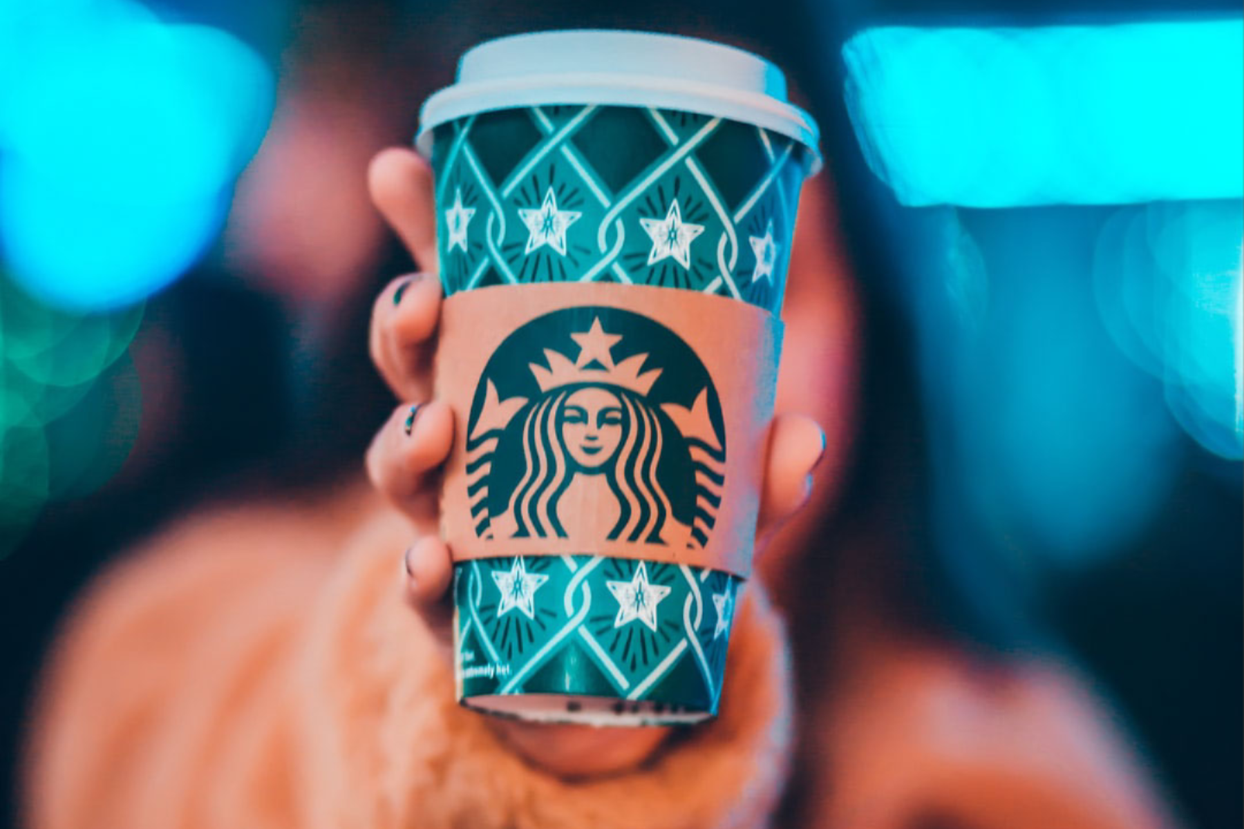 Woman holding out a Starbucks Coffee Cup