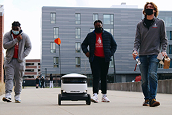 Students walking next to Starship Robot